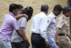 Police officials escort an accused, head covered with black cloth, in the gang rape of a young photojournalist in Mumbai, India, Saturday, Aug. 24, 2013.
