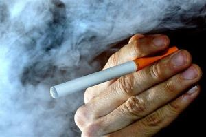 A person poses with an electronic cigarette.