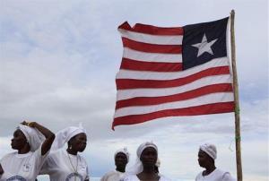 Members of the women in peacebuilding network, started by Nobel Peace Prize winner Leymah Gbowee, sing alongside a Liberian flag .