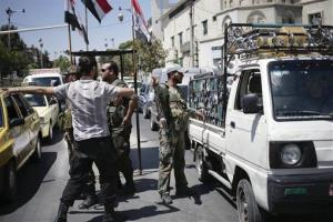 Syrian soldiers check identifications and search vehicles at a checkpoint in Damascus.
