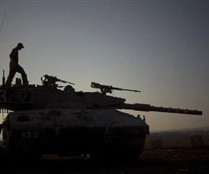 Israeli soldiers work on their tank near the border with Syria on the Golan Heights, July 16, 2013.