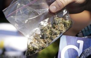 A man pulls out a bag of marijuana to fill a pipe at the first day of Hempfest, Friday, Aug. 16, 2013, in Seattle.