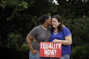 Carina Beckham, left, kisses her partner Kim Gana during a rally for gay marriage, Wednesday, June 26, 2013, on Independence Mall in Philadelphia.
