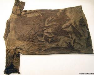 Archaeologists have found a patched, brown tunic in the Norwegian mountains under melting snow patches.