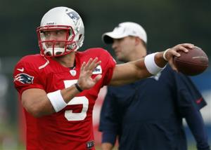 New England Patriots quarterback Tim Tebow throws as offensive coordinator Josh McDaniels watches during a practice in Foxborough, Mass.