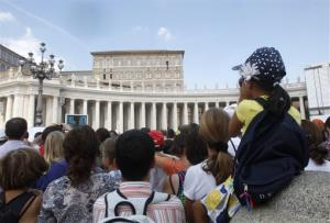 A crowd listens to Pope Francis, seen at the second from right window, reciting the Angelus prayer from his studio window overlooking St.Peter's Square at the Vatican, Sunday, Sept. 1, 2013.