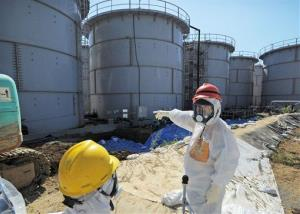 Japanese Trade Minister Toshimitsu Motegi, right, in protective gear inspects storage tanks at the Fukushima Dai-ichi nuclear plant.