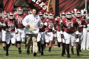 The Arkansas Razorbacks run onto the field before a game against Louisiana-Lafayette in Fayetteville.