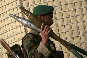 An Afghan security officer carries six rocket-propelled grenades.