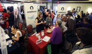 In this Aug. 14, 2013, file photo, people check out opportunities during a job fair in Miami Lakes, Fla.