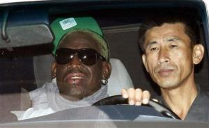 Retired NBA star Dennis Rodman, left, sits in a car as he heads to Pyongyang airport Saturday.