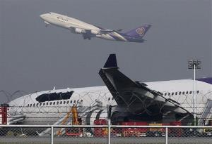 A Thai Airways passenger plane takes off over a damaged Thai Airways Airbus A330-300 at Suvarnabhumi International Airport in Bangkok, Thailand, Monday, Sept. 9, 2013.