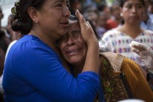 An unidentified woman is comforted as she weeps for a dead relative who was a passenger on a bus that plunged into a deep river canyon in San Martin Jilotepeque, northwest Guatemala.