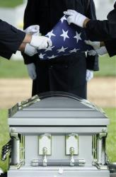 An American flag is folded over the casket of a soldier.