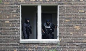 Police officers search an abandoned building in Detroit after yesterday's escape.