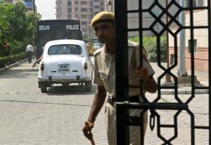An Indian policemen closes the gate of the court after a van carrying the four men entered.