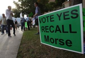 Protestors in favor of recalling Colorado Sen. John Morse post signs near a polling area during the recall election.