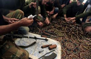 In this Wednesday, Nov. 14, 2012 file photo, Free Syrian Army fighters clean their weapons and check ammunition at their base on the outskirts of Aleppo, Syria.