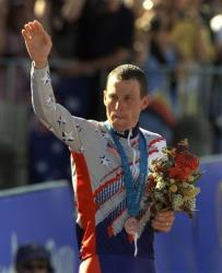 In a Sept. 30, 2000, photo, Lance Armstrong waves after receiving the bronze medal in the men's individual time trials at the 2000 Summer Olympics in Sydney.
