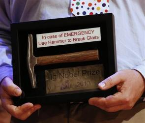 A winner holds an Ig Nobel Prize during the annual Ig Nobel prize ceremony at Harvard University in Cambridge, Mass. Thursday, Sept. 12, 2013.