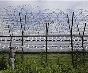 A South Korean man adjusts the national flags on the military wire fence at the Imjingak Pavilion near the border village of Panmunjom, which has separated the two Koreas since the Korean War.