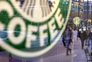 In this Wednesday, Jan. 26, 2011, file photo, pedestrians are reflected outside a Starbucks store in Atlanta.