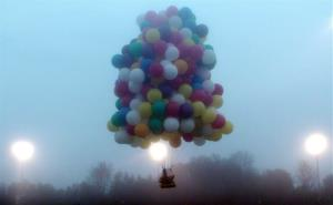 In this photo provided by Mark McBreairty, a balloon cluster carrying Jonathan Trappe lifts off from Caribou, Maine, Thursday.