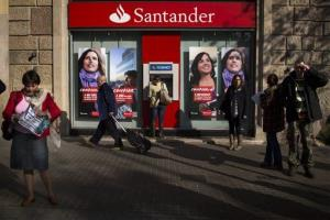 People walk past a branch of Santander bank in Barcelona, Spain, in this file photo.