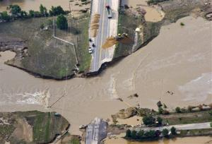 A road crew works on a stretch of highway washed out by flooding along the South Platte River in Weld County, Colorado near Greeley, Saturday, Sept. 14, 2013.  Hundreds of roads in the area have been damaged or destroyed by the floodwaters that have affected parts of a 4,500-square-mile...