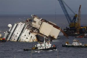 Tow boats sail past the Costa Concordia ship as it lies on its side near the Tuscan Island of Giglio, Italy, Sunday, Sept. 15, 2013.