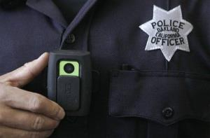 Oakland Police officer Huy Nguyen shows a video camera worn by some officers in Oakland, Calif.