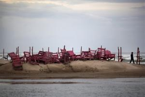 A man walks past tied up chairs at the Miramar beach as Hurricane Ingrid approaches the coast in Ciudad Madero, Mexico, Sunday Sept. 15, 2013.