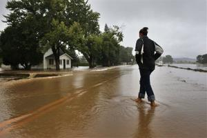 A local woman walks in an evacuated neighborhood where many homes are inundated with water from overflowing canals after days of flash floods and intense rain, in Hygiene, Colo., Sept. 15, 2013.