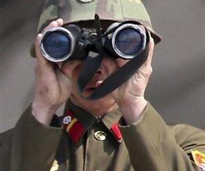 A North Korean soldier uses a pair of binoculars to watch the South Korean side.