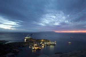 The Costa Concordia is seen after it was lifted upright on the Tuscan Island of Giglio, Italy, early Tuesday morning, Sept. 17, 2013.