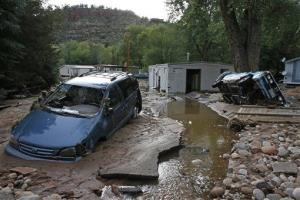 In this Sept. 13, 2013 file photo, cars lay mired in mud deposited by floods in Lyons, Colo.