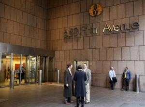 People stand near an entrance to 650 5th Ave. in New York in this file photo.