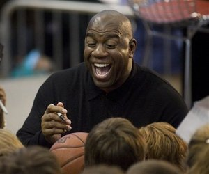 Basketball player Earvin Magic Johnson laughs as he signs autographs.