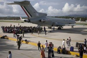 Hundreds of stranded tourists gather around a Mexican Air Force jet as they wait to be evacuated, at the air base in Pie de la Cuesta, near Acapulco, Mexico.