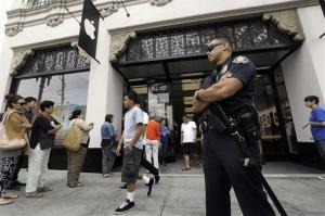 A police officer guards the entrance of the Apple store as customers wait in line in Pasadena.