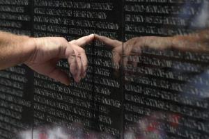 A visitor to the Vietnam Veterans Memorial touches the name of a fallen soldier.
