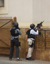 Armed special force aim their guns at the Westgate Mall in Nairobi, Kenya on Saturday, Sept. 21 2013, after gunmen threw grenades and opened fire during an attack that left multiple dead and dozens wounded. A witness to the attacks on the upscale shopping mall says that gunmen told Muslims...