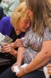 Peggy Eddington-Smith, 69, of Dayton, Nev., and Donna Gregory of St. Louis hug during a ceremony in Dayton, Nev., on Saturday.