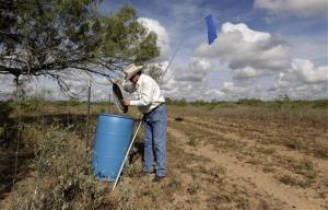 In this Aug. 23, 2013, photo, rancher Lavoyger Durham checks a 55-gallon he keeps filled with water jugs and marked by a flag on his ranch, near Falfurrias, Texas.