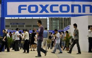 Visitors to a job fair walk past the Foxconn recruitment area in Shenzhen in south China's Guangdong province.