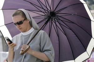 A nun uses her mobile phone as she waits for Pope Benedict XVI's Angelus prayer from his studio overlooking St. Peter's square at the Vatican, Sunday, June 17, 2012.