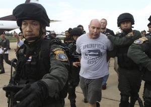 Joseph Hunter, center, is led by Thai police commandos after his arrest in Bangkok, Thailand.