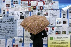 A woman looks at a display of missing people posted at an event organized by a television station to highlight the issue in Hangzhou, eastern China's Zhejiang province.