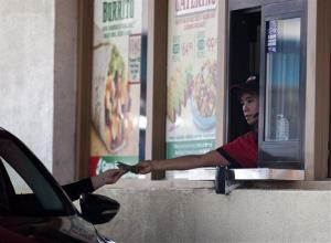 A Carl's Jr. employee gives a customer change through a drive-thru window in San Diego on Friday, Sept. 13, 2013.