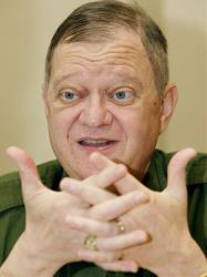 Author Tom Clancy, the hawkish master of military thrillers, gestures during an interview in this Monday, May 24, 2004, file photo in New York.